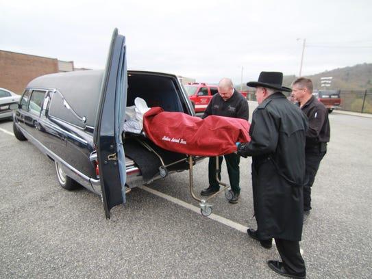 Reenactors roll the body of a drunk driving victim