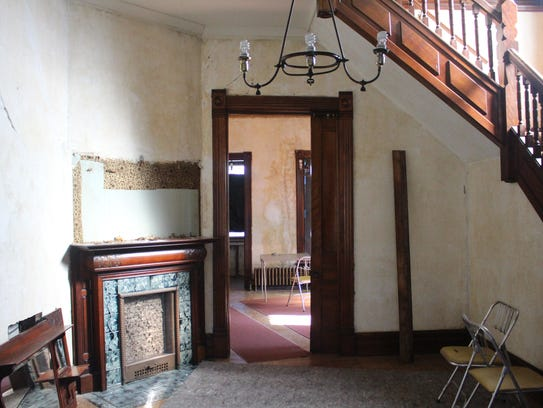 An overmantel has been pried off the wall above the