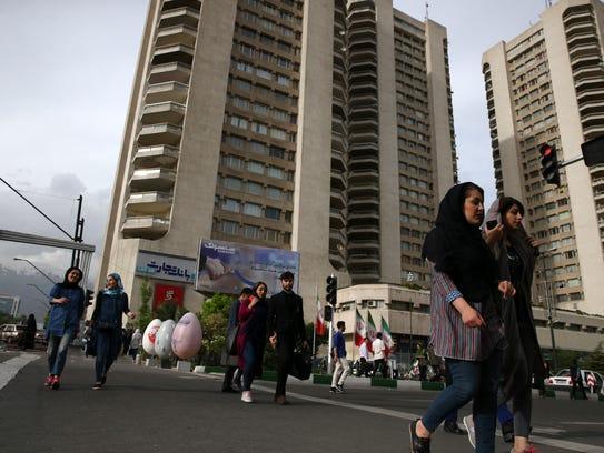 Pedestrians cross Mirdamad Boulevard in north Tehran,