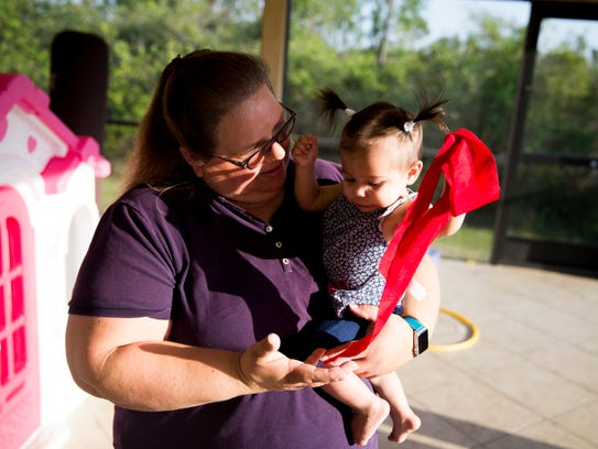 Kara Jansen holds one of her two foster daughters in her arms while the rest of her kids play on the family's lanai Monday, May 7, 2018 in rural Collier County.