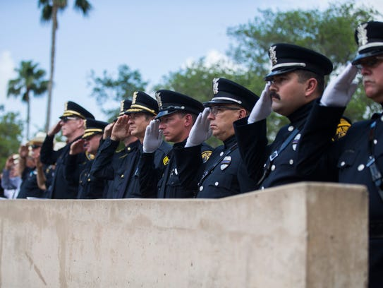 Corpus Christi police officers salute during a ceremony