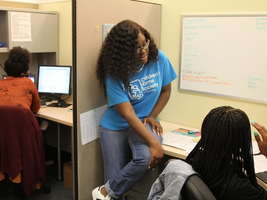 Edna Francois, 31, a dependency case manager supervisor at Children's Home Society, talks with a case manager she supervises in the Old Bainbridge office Wednesday. Francois was recognized by CHS for her leadership on Child Welfare Professionals Recognition Day.