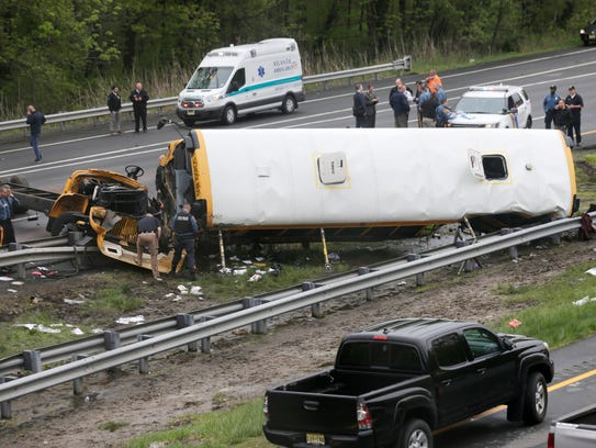 Emergency personnel work at the scene of a school bus