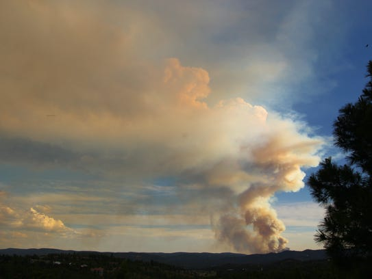 The Soldier Canyon Fire sends a plume of smoke into the sky near sunset Thursday.