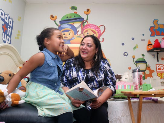 Jacqueline Borrero reads a book with her daughter Mariah