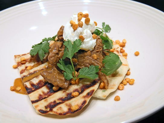Red Curry Braised Goat is served over naan at Braise. (Photo: Michael ...