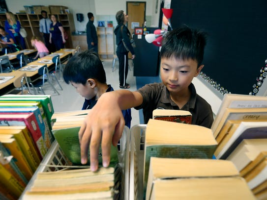 Loic Yu, 9, looks through the classroom books next