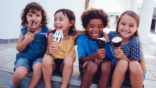 Multi-ethnic best friends children eating ice-cream and having fun on summer holidays