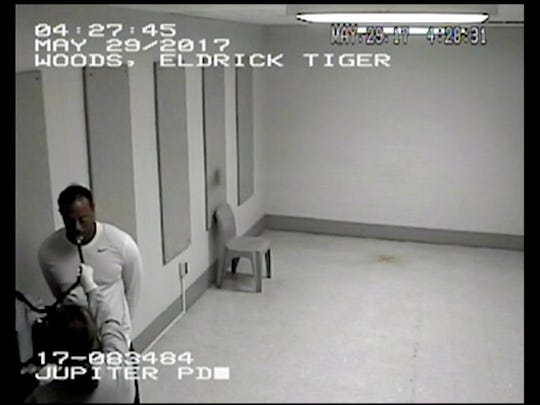 In this Monday, May 29, 2017, image made from a surveillance video provided by the Jupiter Police Department, Tiger Woods uses a breathalyzer at the Palm Beach County jail following his DUI arrest in Palm Beach County, Fla. Woods told the officers he had not been drinking, and two breath tests at the jail registered a 0.0 blood-alcohol level. Woods is to be arraigned July 5 in Palm Beach County Court.