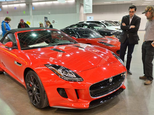 Jaguar of Minneapolis representative Joe Baker, right center, talks with William Hollermann of Little Falls about a new $95,720 Jaguar F-Type S Convertible Saturday during the Central Minnesota New Car Show at the River's Edge Convention Center. The car has a 380-horsepower V-6 motor and can approach speeds of about 170 mph.