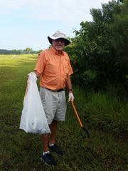 Tom Venskus of Estero helps collect litter during the annual coastal cleanup on Lovers Key, Saturday, Sept. 17.
