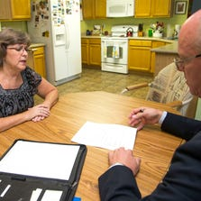 Peggy Indrelunas talks to her financial planner Mike Konen at her house in Chandler.