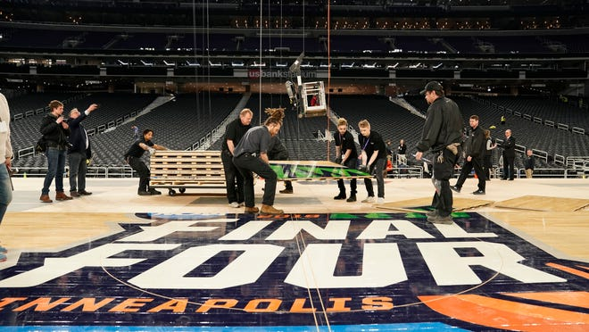 U.S. Bank Stadium operations crew installs the court for the NCAA Final Four college basketball tournament in Minneapolis, Friday, March 29, 2019.  (Leila Navadi/Star Tribune via AP) ORG XMIT: MNMIT103