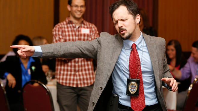Nick Rowley, playing the role of detective Richard Less, gets excited over clues during The Dinner Detective event.