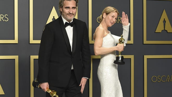 """Joaquin Phoenix, winner of the award for best performance by an actor in a leading role for """"Joker"""", left, and Renee Zellweger, winner of the award for best performance by an actress in a leading role for """"Judy"""", pose in the press room at the Oscars on Sunday, Feb. 9, 2020, at the Dolby Theatre in Los Angeles. (Photo by Jordan Strauss/Invision/AP)"""