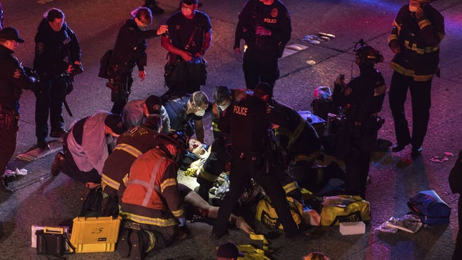 Emergency workers tend to an injured person on the ground after a driver sped through a protest-related closure on the Interstate 5 freeway in Seattle, authorities said early Saturday. Dawit Kelete, 27, has been arrested and booked on two counts of vehicular assault.