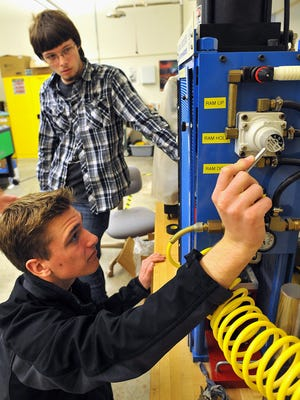 Butler County Community College sophomores Zach Staebler, front, and Mike Paul work an injection molding machine in the school's manufacturing lab. (Bob Donaldson/Pittsburgh Post-Gazette/TNS)