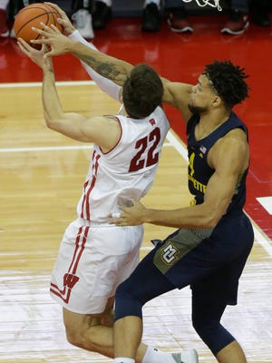 Marquette forward Theo John defends against Wisconsin forward Ethan Happ in the Golden Eagles' victory on Dec. 9.