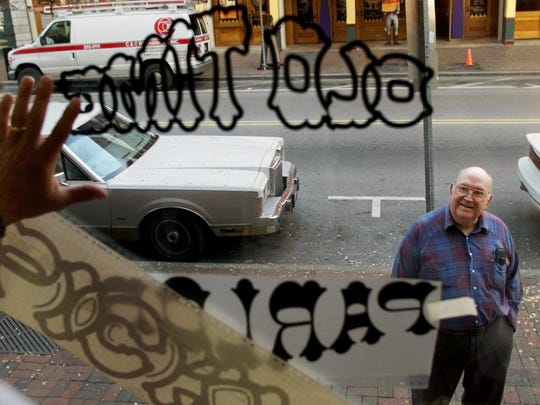 Bluegrass legend Tut Taylor watches his son-in-law place the sign for the new Old Time Pickin' Parlor on the window in 2000. The venue closed in 2002.