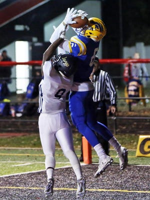 Newport Central Catholic receiver Trent Wrobleski makes a leaping catch over Lloyd defensive back Demarco Giles.
