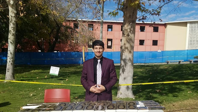 Mojtaba Noor, a business student at New Mexico State University, hands out free copies of the Quran outside Corbett Center on Dec. 2, 2016. Noor purchased about 300 copies of the Islamic holy book in hopes of contributing to a better understanding of his religion in the community.