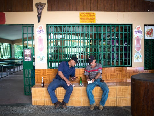 People drink beer in a lechonera, an open-air restaurant