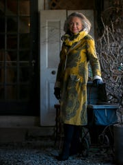 Jan Geddes wears a grey and yellow Moth sweater coat; grey sleeveless Ralph Lauren dress; and black high-heel Coley boots.