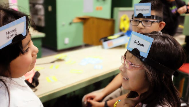 From left, Judith Hernandez, 7, Esmeralda Matias, 7, and Alfredo Matias, 9, play a word-guessing game at the Breadbox Recreation Center in Salinas.