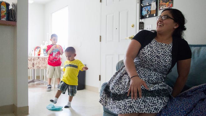 Sandra Godinez laughs as her sons Ricardo Jr., 6, and Ricardo III, 2, play in their Phoenix apartment on Wednesday, June 29, 2016. Godinez and her family got back on their feet with the help of the Temporary Aid to Needy Families program.