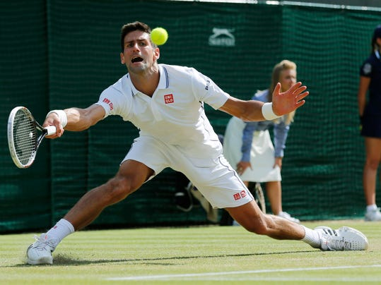 Novak Djokovic of Serbia plays a return to Marin Cilic of Croatia during their men's singles quarterfinal match at the All England Lawn Tennis Championships in Wimbledon, London, Wednesday, July 2, 2014. (AP Photo/Ben Curtis)