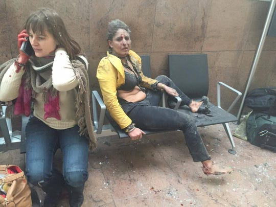 Injured women await aid following twin blasts at Brussels