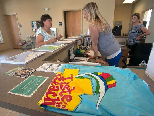 Drucilla Heins, left, learns more about area attractions from Nicole Stacey, cener, and Alison Westmoreland, right, while visiting the ensacola Beach Visitors Information Center Monday afternoon Aug. 22, 2016.