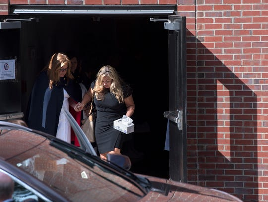 A nurse helps Heather Melton to her car Tuesday, October