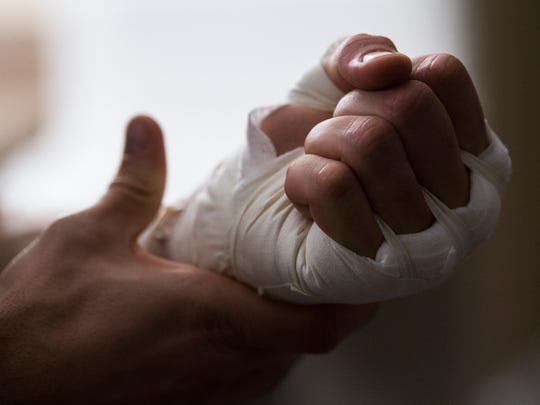 Hilmar Skagfield, of Tallahassee, Fla., adjusts the pressure of his hand wrap Saturday, Jan. 6., 2018, in preparation for his match against MMA fighter Charlie Allen during the second annual Black Tie and Boxing event at the Carl Perkins Civic Center in Jackson. All proceeds benefited the Juvenile Diabetes Research Foundation.