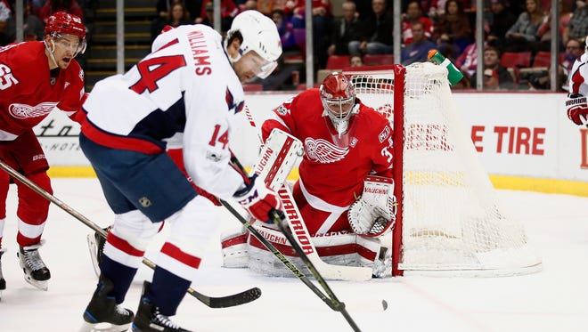 Red Wings goalie Petr Mrazek keeps an eye on the puck next to Justin Williams of the Capitals during the first period at Joe Louis Arena on Feb. 18, 2017 in Detroit.