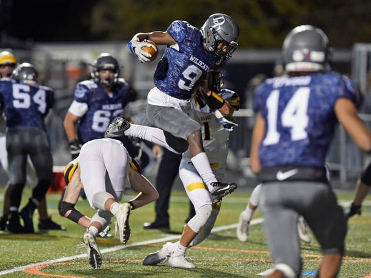 Dallastown's Nyzair Smith leaps over Red Lion's Zachary Crossland on his way to a touchdown in the second half of a YAIAA football game Friday, Nov. 3, 2017, at Dallastown. Dallastown defeated Red Lion 40-27.