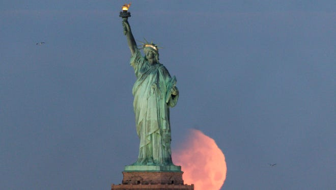 The moon sets behind the Statue of Liberty in New York City Jan. 31.