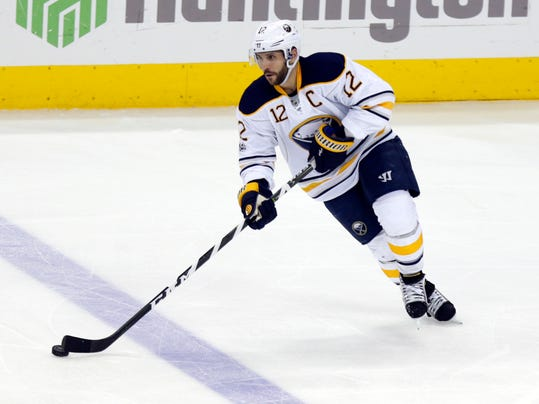 FILE- This March 28, 2017, file photo shows Buffalo Sabres forward Brian Gionta carrying the puck against the Columbus Blue Jackets during an NHL hockey game in Columbus, Ohio.  For someone once constantly reminded of being too small to have an NHL future, Gionta is enjoying a few last laughs entering the twilight of his career. At 38, the 5-foot-7, 180-pound forward has no regrets with the decision he made last summer to put family and flag first to forego a chance at playing a 17th NHL season. Rejecting at least one contract offer in July because it would've meant relocating his wife and three children, Gionta chose to pursue an opportunity to represent the United States at the Winter Olympics in Pyeongchang, South Korea, in February. (AP Photo/Paul Vernon, File)