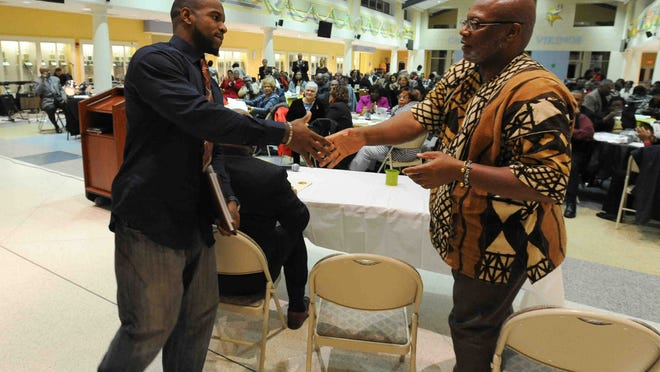 "Panelist Leroy Mann, III (left) and Joe Rufus Brake Jr. shake hands after Mann's speech at ""The Quest for Equality-A Journey of Faith"" panel discussion hosted by the Dr. Martin Luther King, Jr. Celebration Committee at Cape Henlopen High School."