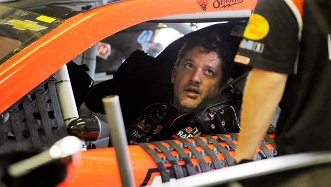 Sprint Cup Series driver Tony Stewart talks to a crew member during practice for Sunday's NASCAR Sprint Cup Series auto race at Atlanta Motor Speedway, Saturday, Aug. 30, 2014 in Hampton, Ga. (AP Photo/David Tulis)
