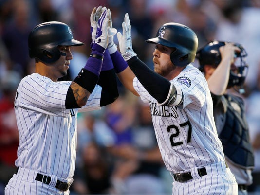 Colorado Rockies' Carlos Gonzalez, left, congratulates Trevor Story as Story heads to the dugout after hitting a two-run home run off New York Yankees starting pitcher Nathan Eovaldi during the fourth inning of a baseball game Tuesday, June 14, 2016, in Denver. (AP Photo/David Zalubowski)