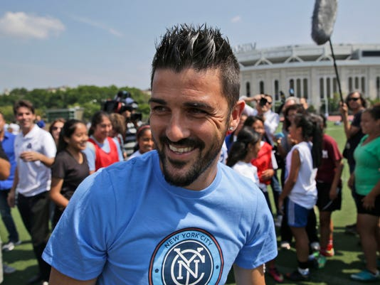 FILE - In this July 31, 2014 file photo, David Villa plays soccer with kids from the South Bronx United program in front of Yankee Stadium in New York. The A-League kicks off its 10th season with a new star attraction - Spanish striker David Villa for a 10-match stint - while some of the marquee men of the last several seasons, including Alessandro Del Piero, are gone. (AP Photo/Seth Wenig, File)