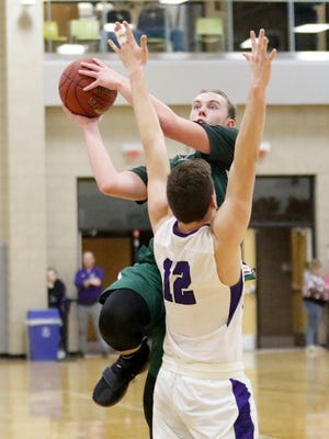 Josh Wood of Newfield puts up a shot in front of Kevin Cunningham of Union Springs on Thursday during the IAC Small School championship game at Tompkins Cortland Community College.
