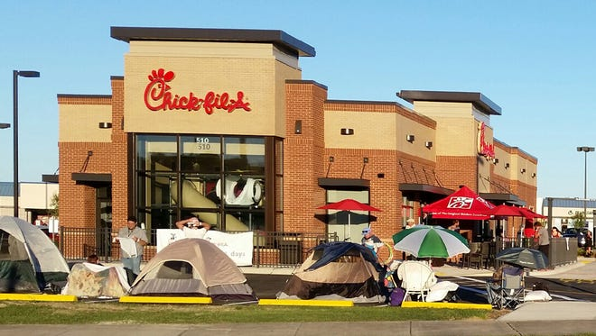 Dozens of people camp out in tents and line the new Chick-fil-A at 510 N. Navy Blvd. Wednesday afternoon in preparation for Thursday's grand opening. The first 100 adults in line by 6 a.m. will win a free one-year supply of meals.