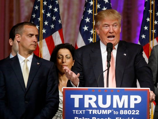 In this March 15, 2016 file photo, Donald Trump's campaign manager Corey Lewandowski listens at left as Trump speaks in Palm Beach, Fla.