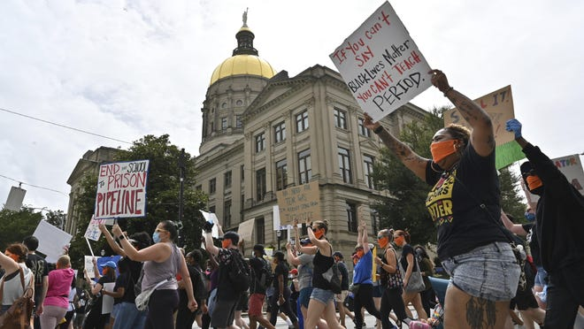 Educators march past the Georgia Capitol during the last day of the legislative session last month.