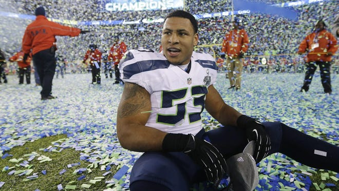Seattle's Malcolm Smith sits on the field after the Seahawks beat the Denver Broncos in the Super Bowl on Feb. 2, 2014, in East Rutherford, N.J. Smith has signed with the Browns.