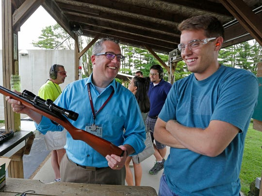 Gun instructor Matthew Wallner smiles, left, as he