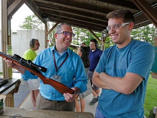 Gun instructor Matthew Wallner smiles, left, as he has a light moment with Jordan LaPean of Kohler during the Coastal Gun Safety Seminar Tuesday July 12 at the Sheboygan Rifle and Pistol Club near Haven.
