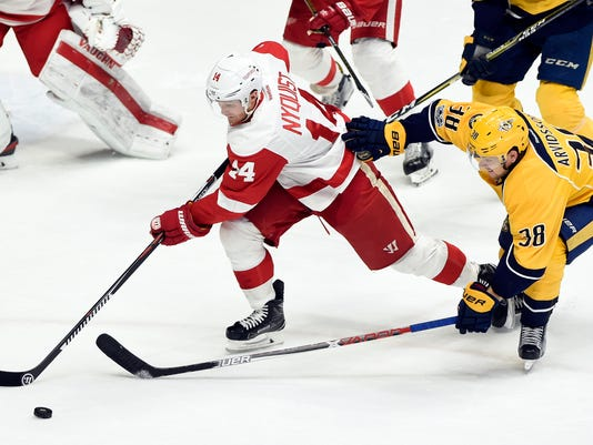 Detroit Red Wings right wing Gustav Nyquist (14), of Sweden, and Nashville Predators left wing Viktor Arvidsson (38), also of Sweden, chase the puck during the second period of an NHL hockey game Saturday, Feb. 4, 2017, in Nashville, Tenn. (AP Photo/Mark Zaleski)
